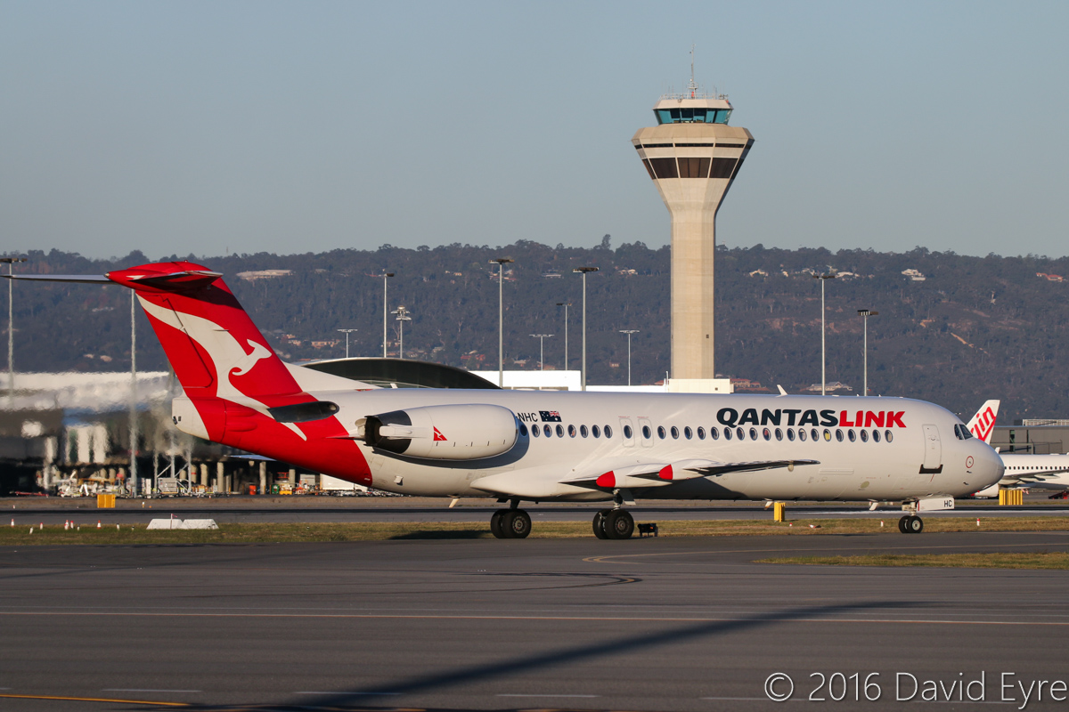 VH-NHC Fokker 100 (MSN 11481) of QantasLink (Network Aviation), at Perth Airport - Thu 2 June 2016. Taxying to runway 03 at 4:35pm, for a flight to Karratha. Control tower in the background. Photo © David Eyre