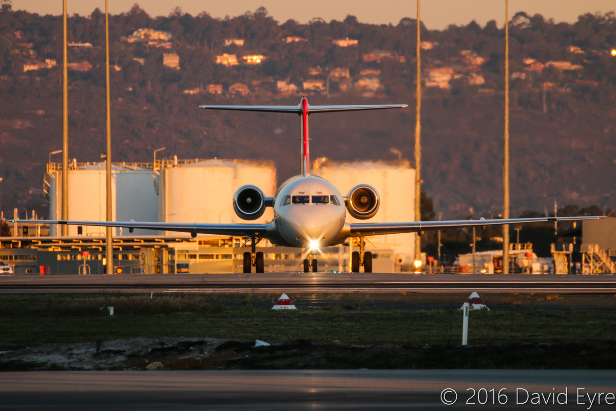 VH-NHM Fokker 100 (MSN 11449) of Network Aviation, at Perth Airport– Thu 2 June 2016. Just landed on runway 03 and crossing runway 06 after arriving from Karratha at 5:10pm. Photo © David Eyre