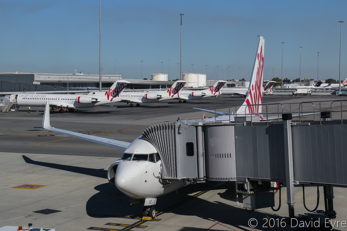 VH-VBZ Boeing 737-7FE (MSN 34322/1777), named 'Cronulla Beach', of Virgin Australia at Perth Airport – Thu 2 June 2016. One of only two remaining 737-700s in the fleet, with a row of four Fokker 100s behind. Flight VA1855 to Kalgoorlie, parked at Bay 145 at 3.40pm. Photo © David Eyre