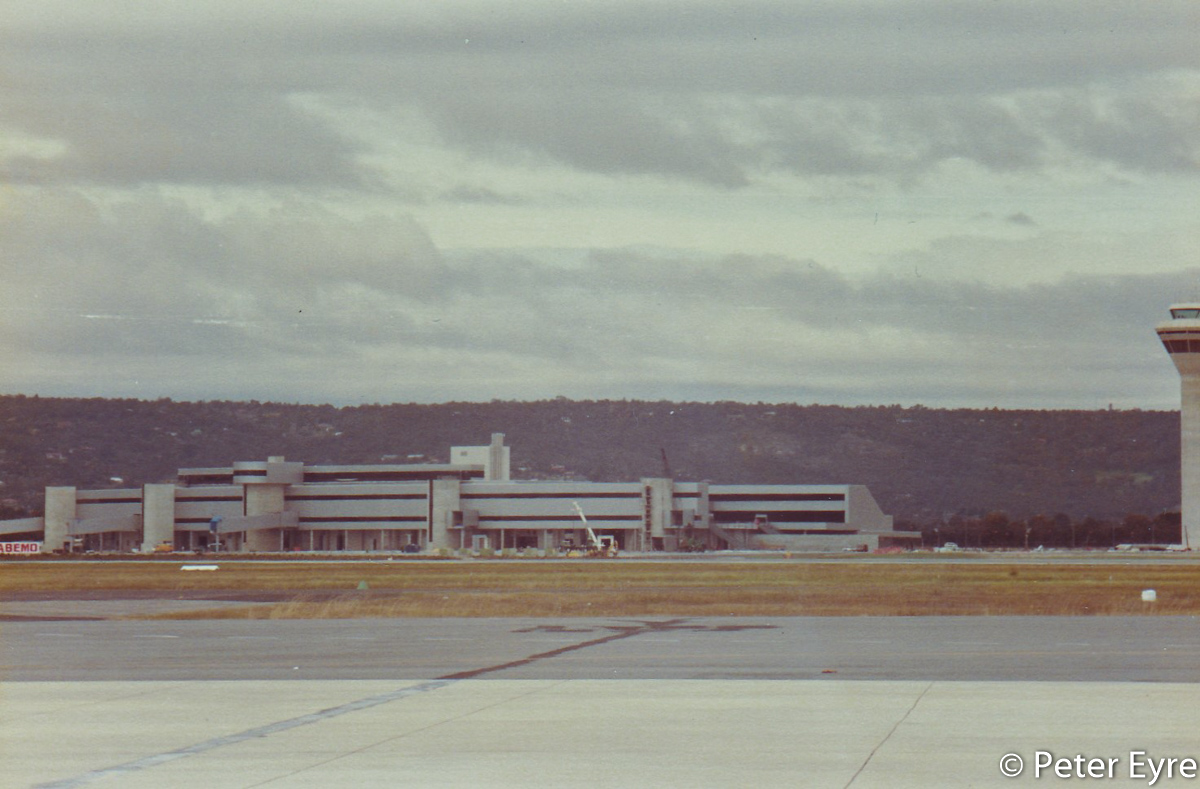 The new International Terminal, later Terminal 1 International, under construction, at Perth Airport - 10 August 1986. Construction of the aerobridges has commenced. Photo taken from the old international apron, where Terminal 3 is now located. T1 opened on 25 October 1986 and started operations on 27 October 1986. Photo © Peter Eyre