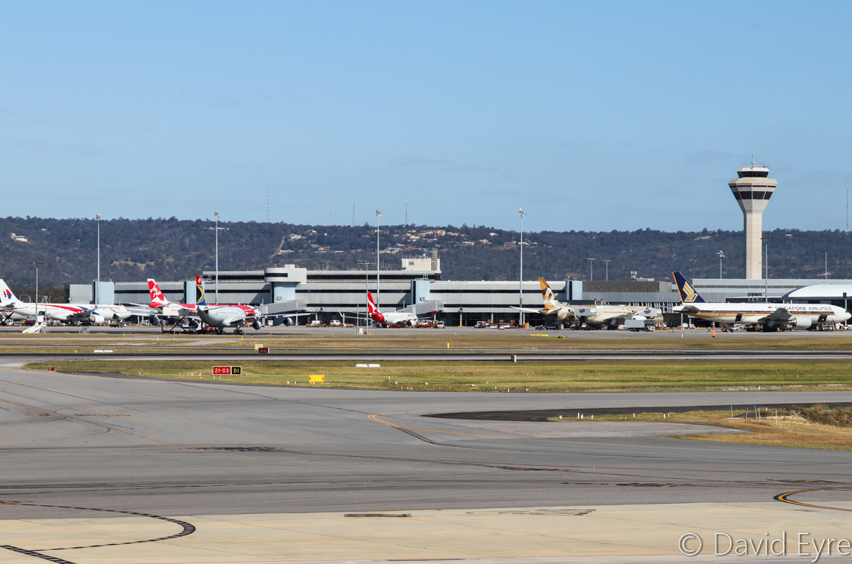 Terminal 1, viewed from Terminal 4, Perth Airport - Fri 28 October 2016. Visible are 9M-MTA Airbus A330-323X of Malaysia Airlines; 9M-XXG Airbus A330-343X of AirAsia X; ZS-SXB Airbus A340-313X of South African Airways; VH-XZF Boeing 737-838 of Qantas; A6-BLI Boeing 787-9 Dreamliner of Etihad; 9V-SRP Boeing 777-212ER of Singapore Airlines. Photo © David Eyre