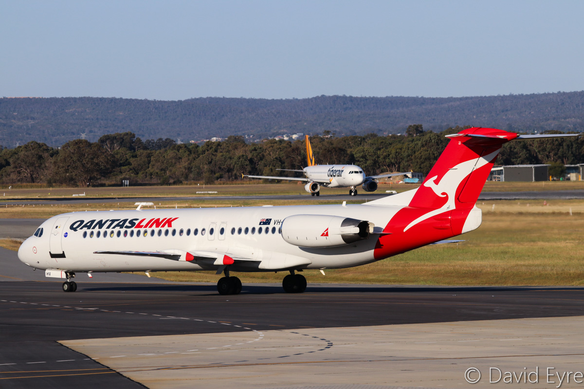VH-NHV Fokker F100 (MSN 11482) of QantasLink (Network Aviation) and VH-VNG Airbus A320-232 (MSN 3674) of Tigerair Australia, at Perth Airport - Fri 28 October 2016. VH-NHV is taxying in after arriving from Degrussa copper mine at 5:23pm, whilst VH-VNG in the background is lining up on runway 21 for takeoff as flight TT416 to Melbourne. Photo © David Eyre