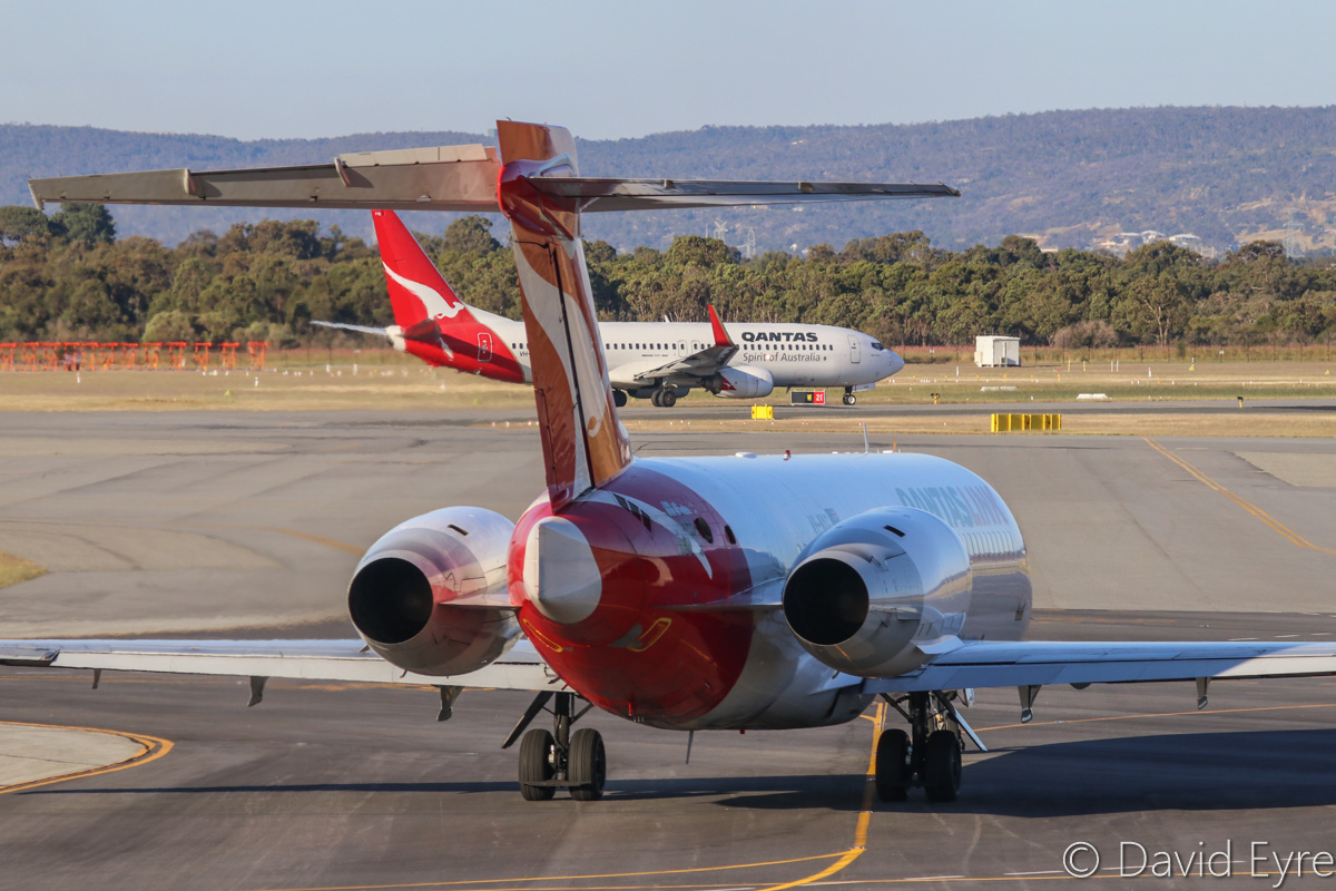 VH-NXG Boeing 717-2K9 (MSN 55057/5020) of QantasLink and VH-VYE Boeing 737-838 (MSN 33993/1712) named 'Alice Springs' of Qantas, at Perth Airport - Fri 28 October 2016. VH-NXG is taxying out to runway 21 at 5:14pm as QF1890 to Kalgoorlie, and in the background is VH-VYE holding short of runway 21 for departure as QF584 to Adelaide. Photo © David Eyre