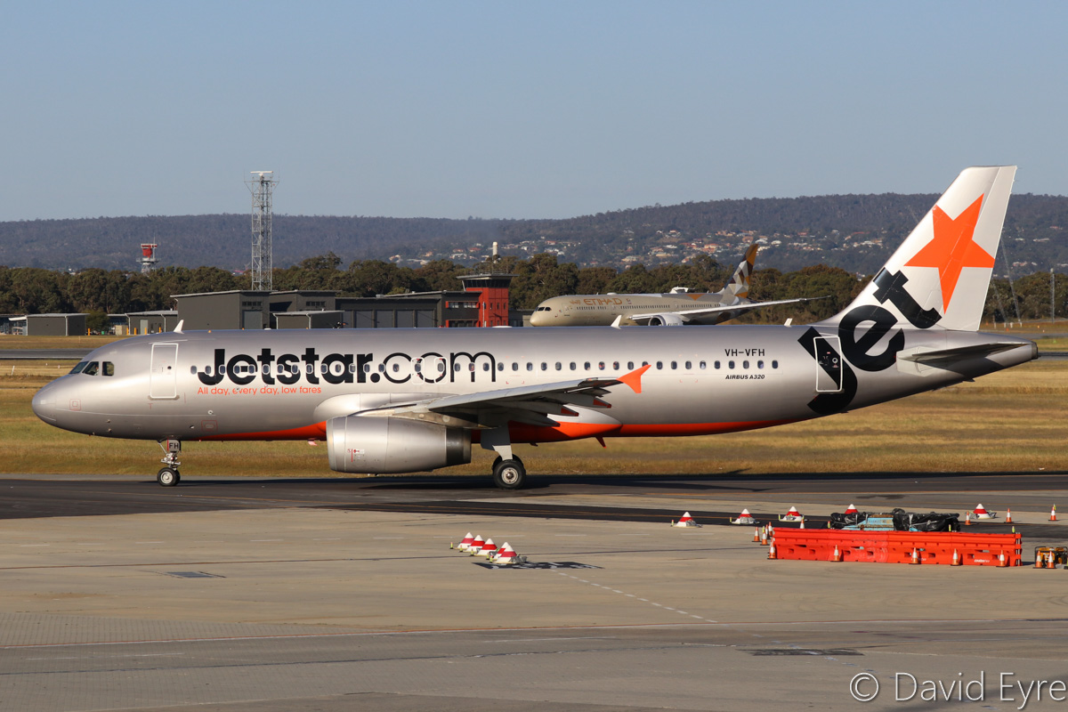 VH-VFH Airbus A320-232 (MSN 5211) of Jetstar and A6-BLI Boeing 787-9 Dreamliner (MSN 39655/459) of Etihad, at Perth Airport - Fri 28 October 2016. VH-VFH is taxying out to runway 21 at 5:09pm as JQ975 to Adelaide, with A6-BLI in the background holding on Taxiway W, short of runway 21, awaiting its turn to line-up for take-off as EY487 to Abu Dhabi. Photo © David Eyre