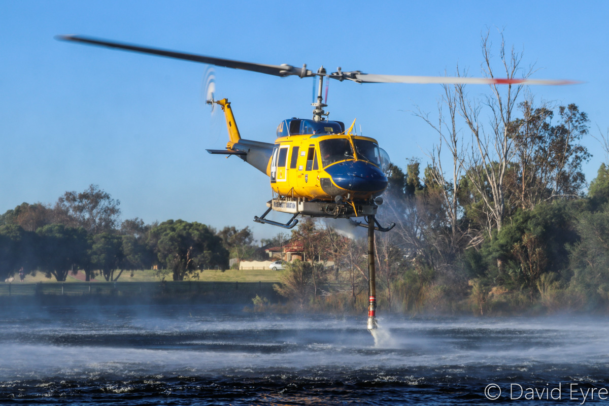 P2-MLJ / HELITACK 674 Bell 214B1 BigLifter (MSN 28066) owned by McDermott Aviation, contracted to the WA Government, at Warradale Park, Landsdale - Wed 23 November 2016. Climbing after refilling its 2,700-litre water tank. Assisting firefighters in fighting a suspiciously-lit bushfire in Lexia, at the Gnangara pine plantation, that burnt through 100 hectares. Built in 1981, ex N2179R, JA9304, N4410N, C-GTWG, F-GJKZ, N214JL. Photo © David Eyre