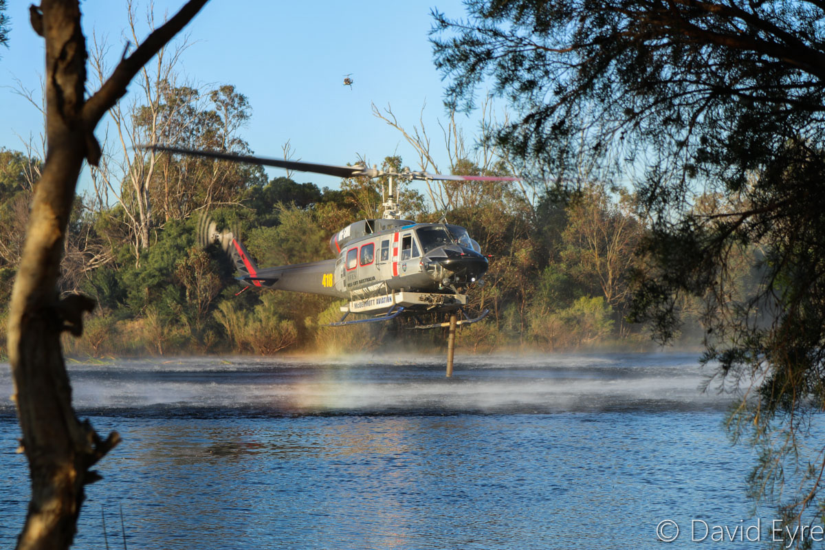 VH-SMI / HELITACK 418 Bell 214B1 BigLifter (MSN 28011) of McDermott Aviation, at Warradale Park, Landsdale – Wed 23 November 2016. Filling up with water from the lake - it can carry 2,700 Litres of water. Assisting firefighters in fighting a suspiciously-lit bushfire in Lexia, at the Gnangara pine plantation, that burnt through 100 hectares. Normally operated for the NSW Rural Fire Service, this firefighting helicopter is currently based at Jandakot, where it was also based for the 2015/16 summer. Built in 1976, ex LN-OSW, P2-OSW, LN-OSW, C-GTWI. Photo © David Eyre