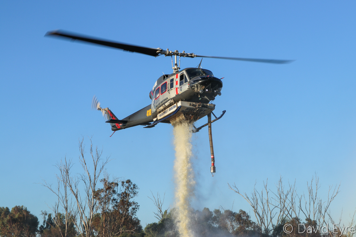 VH-SMI / HELITACK 418 Bell 214B1 BigLifter (MSN 28011) of McDermott Aviation, at Warradale Park, Landsdale – Wed 23 November 2016. Releasing water from its 2,700 Litre tank, having finished with firefighting for the day. It assisted firefighters in fighting a suspiciously-lit bushfire in Lexia, at the Gnangara pine plantation, that burnt through 100 hectares. Normally operated for the NSW Rural Fire Service, this firefighting helicopter is currently based at Jandakot, where it was also based for the 2015/16 summer. Built in 1976, ex LN-OSW, P2-OSW, LN-OSW, C-GTWI. Photo © David Eyre