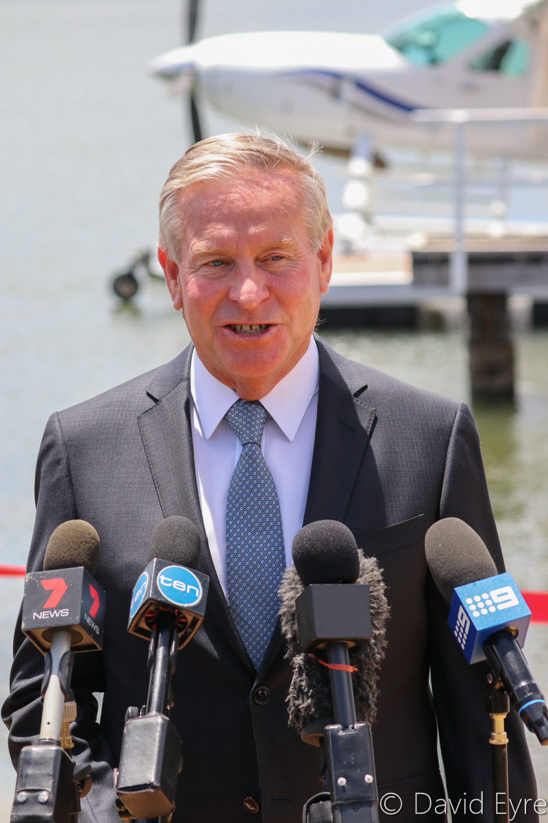 Western Australian Premier and Tourism Minister Colin Barnett announcing the launch of Swan River Seaplanes' seaplane tourism services between Perth's Swan River and Margaret River, Queen Street Jetty, South Perth - Mon 23 January 2017. Behind is VH-MOX Cessna 208 Caravan (amphibious seaplane) (MSN 20800227) operated by Swan River Seaplanes (West Coast Air Services Pty Ltd/Avanova Pty Ltd). Photo © David Eyre