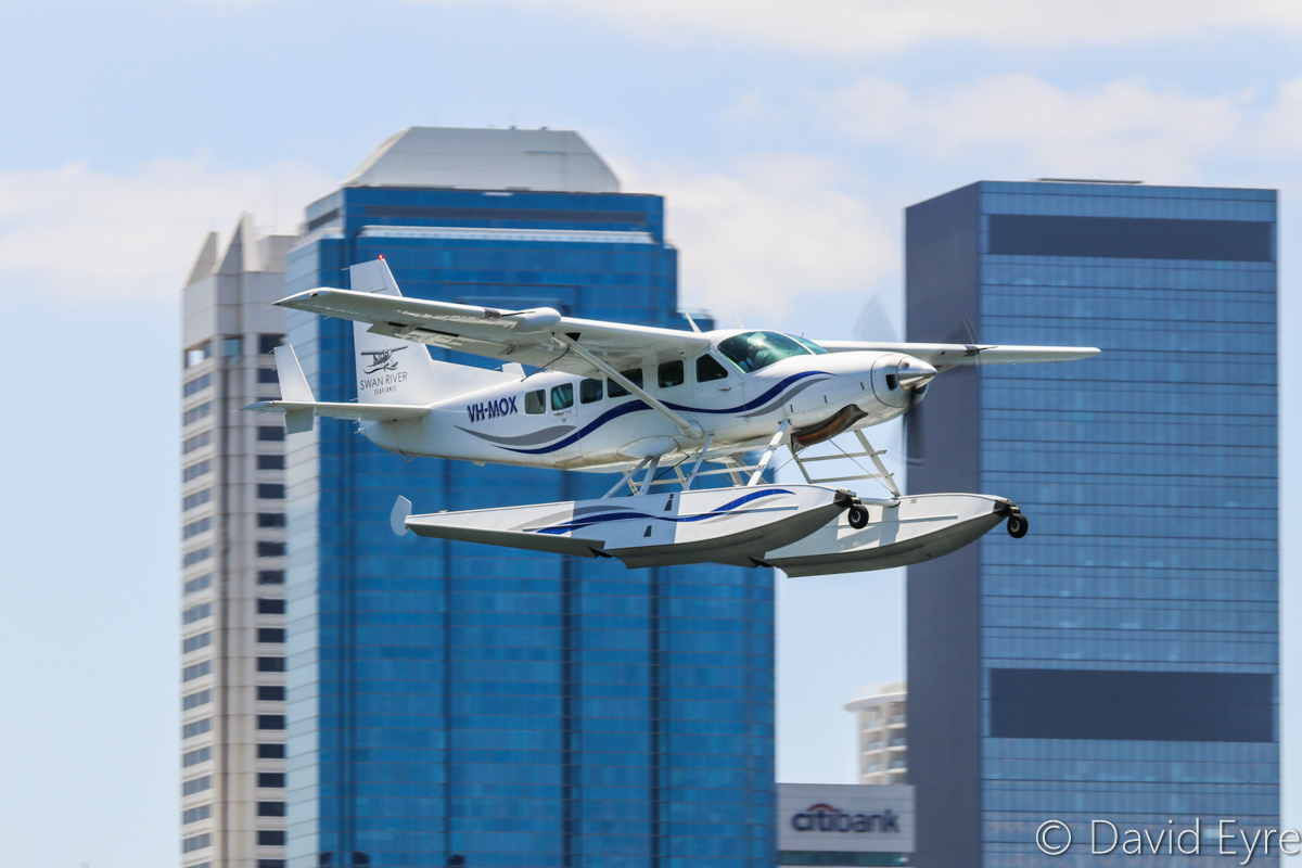 VH-MOX Cessna 208 Caravan (amphibious seaplane) (MSN 20800227) operated by Swan River Seaplanes (West Coast Air Services Pty Ltd/Avanova Pty Ltd), Swan River, South Perth - Mon 23 January 2017. Flying over the Swan River with Perth city as a backdrop at 12:17pm, just after take-off, following the official ceremony to launch seaplane tourism services between Perth's Swan River and Margaret River. Photo © David Eyre