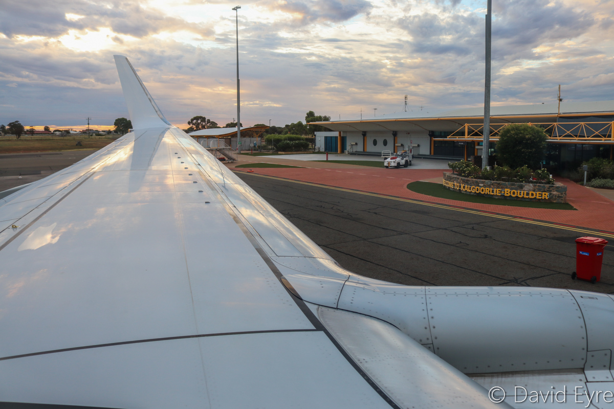Airport Terminal, seen from VH-BZG Boeing 737-8FE (MSN 37822/3355) of Virgin Australia, named 'Vivonne Bay', at Kalgoorlie-Boulder Airport – Wed 22 March 2017. Viewed from seat 13A. the forward overwing exit seat on the left side. Awaiting engine start at 5:44pm for flight VA1858 back to Perth. Engines started at 6:03pm, but we remained there with engines running as air traffic controllers claimed that the flight plan was not showing in their system. We eventually started taxying out at 6:18pm and were airborne at 6:20pm. Photo © David Eyre