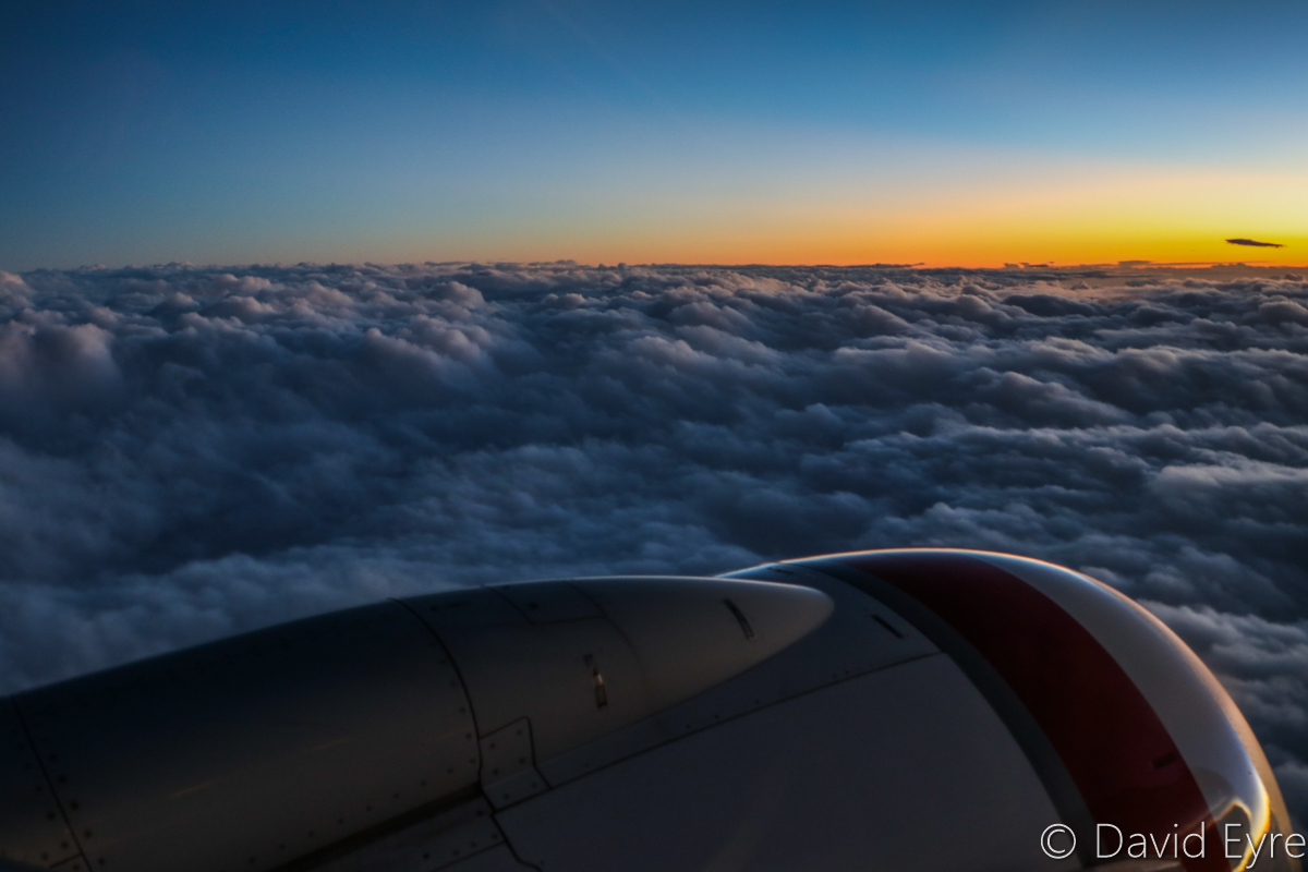 Sunset above clouds near Victoria Rock, seen from VH-BZG Boeing 737-8FE (MSN 37822/3355) of Virgin Australia, named 'Vivonne Bay' – Wed 22 March 2017. Flight VA1858 from Kalgoorlie to Perth. 120km SW of Kalgoorlie-Boulder Airport, at 6:33pm (25 minutes after sunset), 13 minutes after take-off, at 29,000 feet. Viewed from seat 13A, the forward overwing exit seat on the left side. Photo © David Eyre