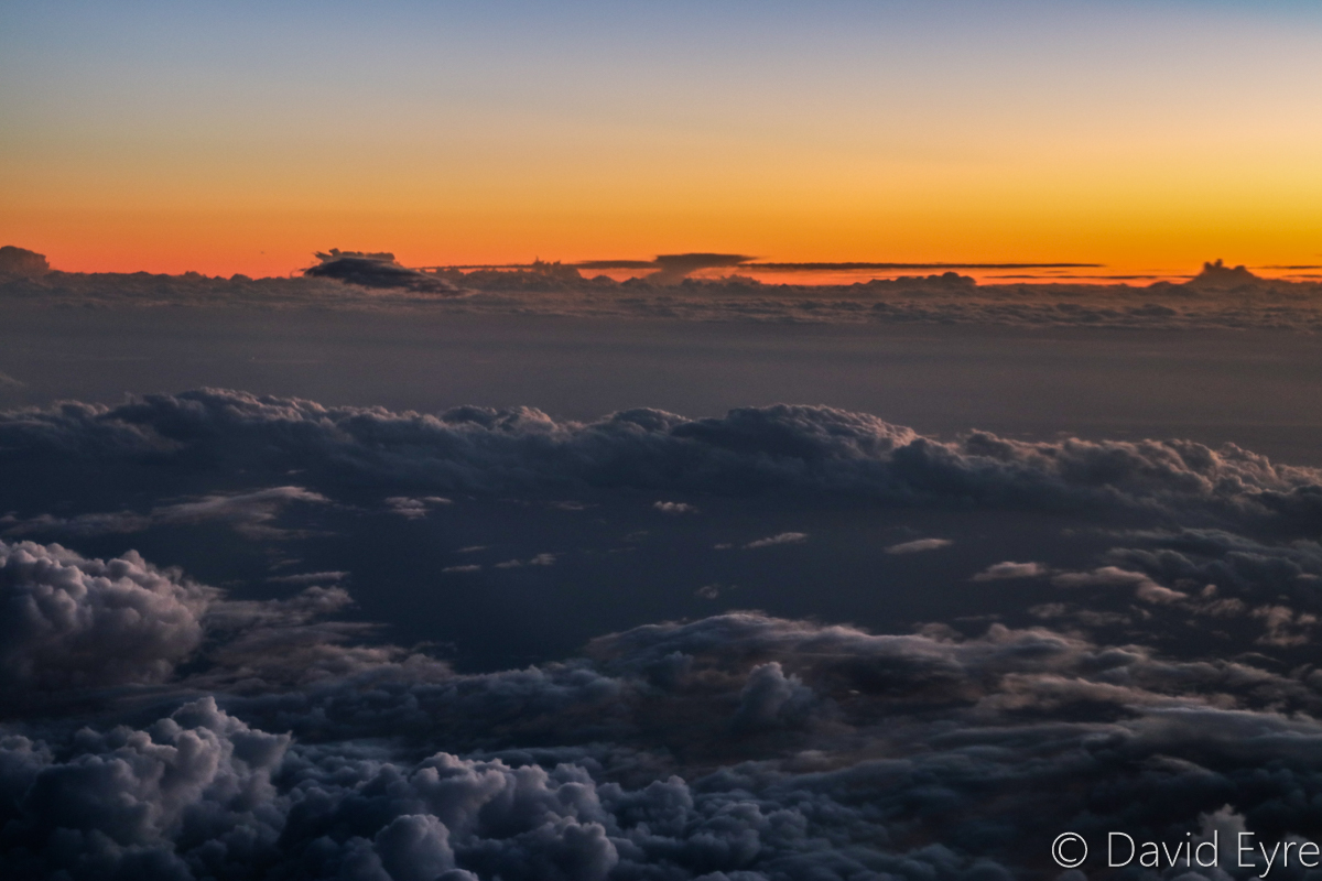 Sunset above clouds near Mount Palmer, seen from VH-BZG Boeing 737-8FE (MSN 37822/3355) of Virgin Australia, named 'Vivonne Bay' – Wed 22 March 2017. Flight VA1858 from Kalgoorlie to Perth. 155km SW of Kalgoorlie-Boulder Airport, at 6:36pm, above 33,000 feet. Viewed from seat 13A, the forward overwing exit seat on the left side. Photo © David Eyre