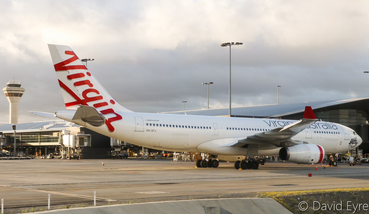 VH-XFJ Airbus A330-243 (MSN 1561) of Virgin Australia, named 'Gnaraloo Bay', at Perth Airport – Wed 22 March 2017. Flight VA556 to Sydney, parked on Bay 148, which departed at 10:39am. Control Tower and Terminal 1 Domestic in the background. Seen from aboard VH-YFW Boeing 737-8FE of Virgin Australia, whilst taxying out as VA1849 to Kalgoorlie at 7:10am. Photo © David Eyre