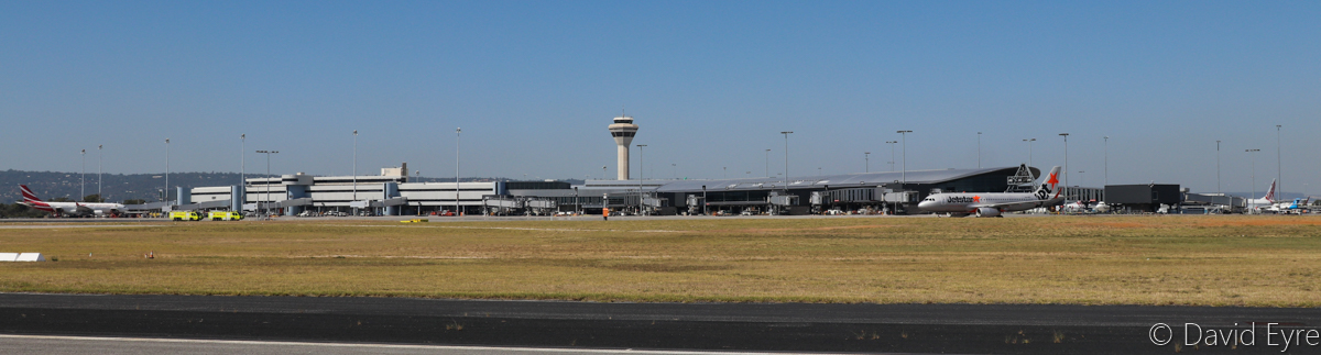 Terminal 1 International and Control Tower at Perth Airport - Wed 5 April 2017. Seen from runway 06/24, near the intersection of runway 03/21. On the left is 3B-NBL Airbus A330-200 of Air Mauritius and VH-VFU Airbus A320-232 of Jetstar, which just arrived from Denpasar (Bali). The two fire trucks on the left are driving to position themselves either side of taxiway T, to provide a water cannon welcome for a special visit by a Singapore Airlines Airbus A350-900, which visited to celebrate 50 years of services to Perth. Photo © David Eyre