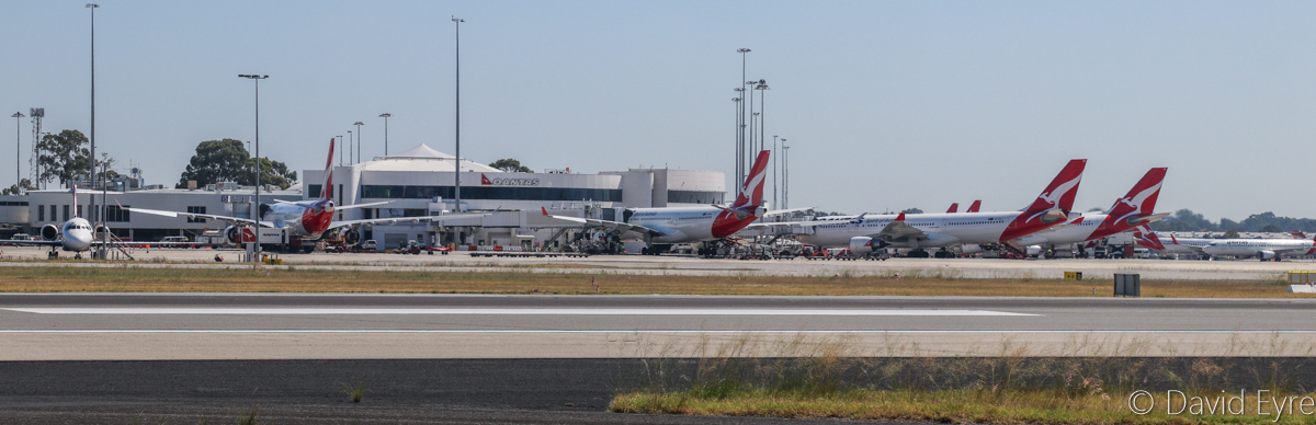 Qantas Terminal 4 at Perth Airport - Wed 5 April 2017. Four Airbus A330-200s, a Boeing 717-200 on the left and Boeing 737-800s on the right. Seen from runway 24 (temporarily closed from installation of Category 3 lighting)), near intersection with runway 21. Photo © David Eyre