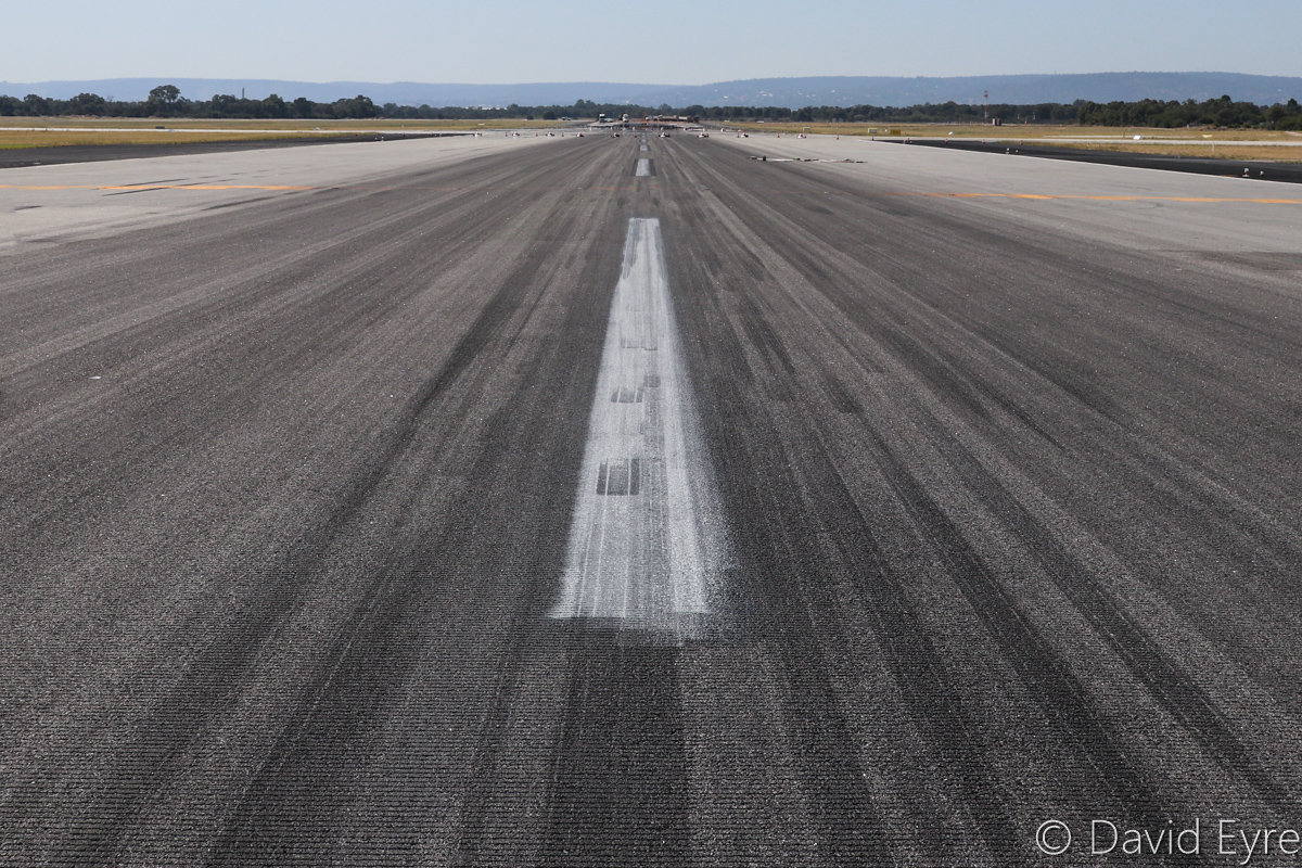 Runway 06 at Perth Airport - Wed 5 April 2017. The runway was temporarily closed on this date, for installation of Category 3 high intensity lighting. Runway 21 is behind the camera and taxiway C is marked by white and red cones. Photo © David Eyre