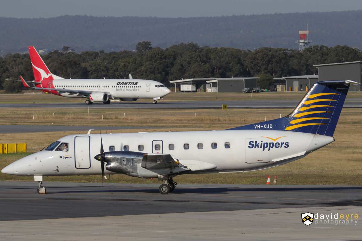 VH-XUD Embraer 120ER Brasilia (MSN 120140) of Skippers Aviation and VH-VYF Boeing 737-838 (MSN 33994/1727) of Qantas, named 'Evandale', at Perth Airport - 1 November 2017. VH-XUD is seen taxying in after arriving from Jundee at 5:13pm. VH-VYF in the background is taking off from runway 21 as flight QF1064 to Kalgoorlie. Photo © David Eyre