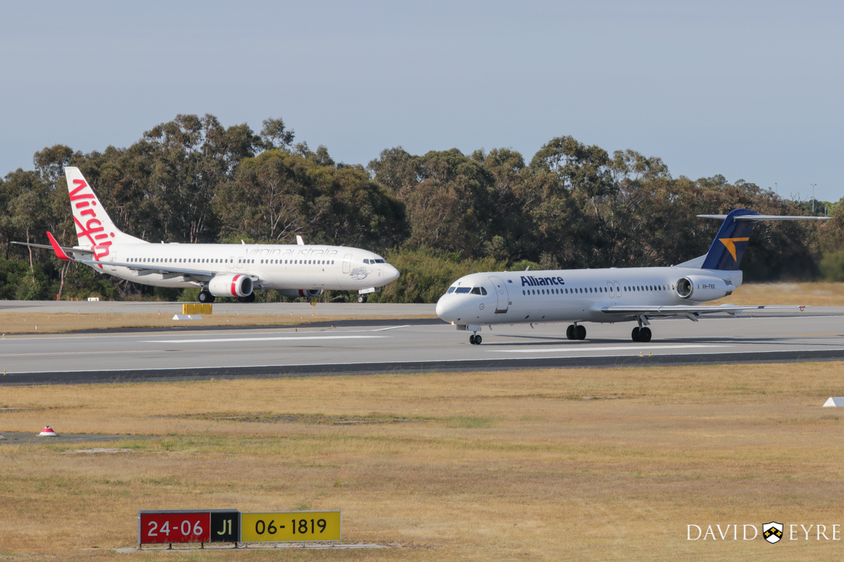 VH-YFE Boeing 737-81D (MSN 39414/3623) of Virgin Australia, named 'Sunshine Beach', and VH-FKK Fokker 100 (MSN 11379) of Alliance Airlines, at Perth Airport - 2 November 2017. VH-YFE is operating flight VA714 to Adelaide and holding short of runway 06, while VH-FKK takes off at 8:19am as flight QQ7874 to Telfer. Photo © David Eyre