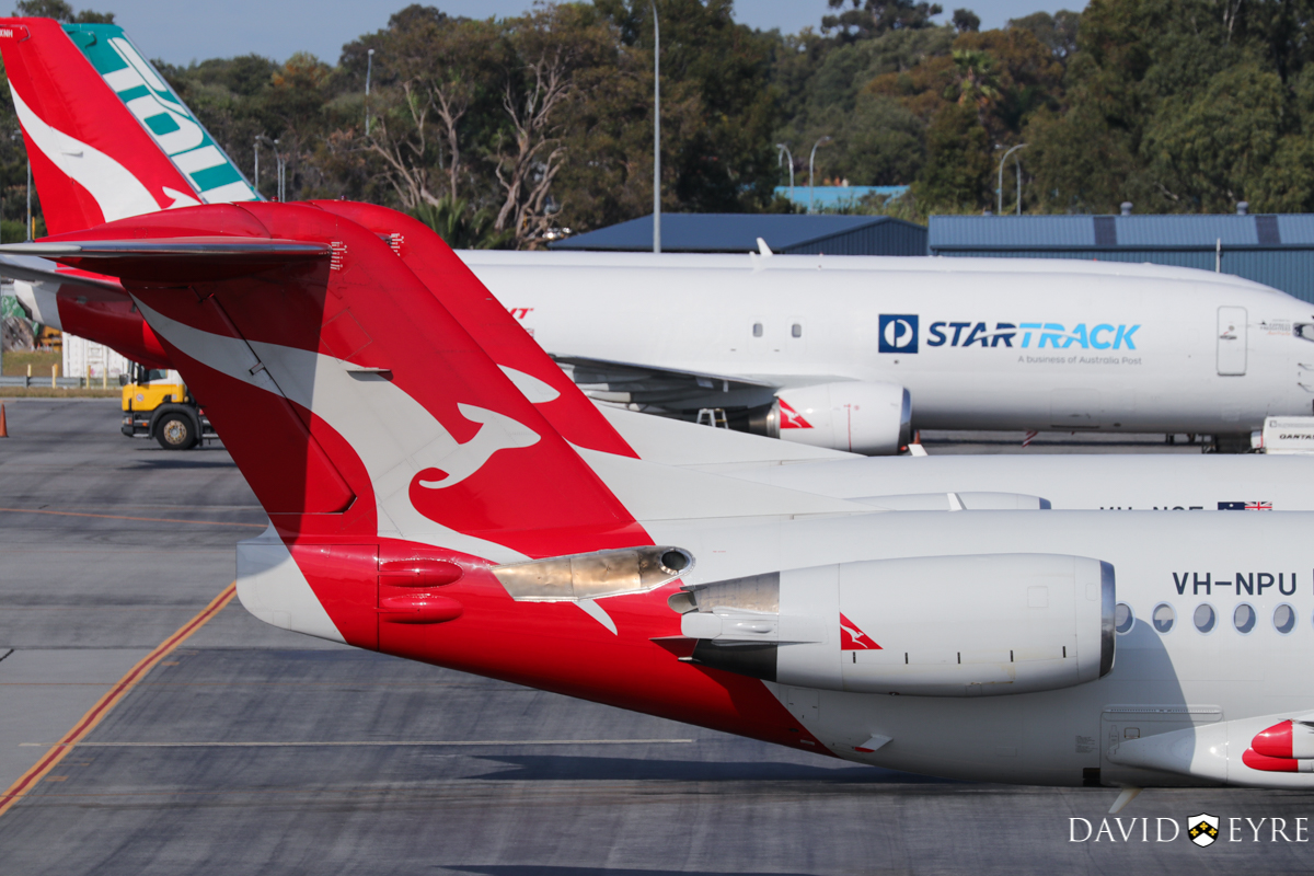 VH-NPU Fokker 100 (MSN 11502) of QantasLink (Network Aviation) at Perth Airport - 2 November 2017. Parked south of Terminal 3. VH-NQE is just behind, with Boeing 737-400(SF) VH-XNH and ZK-TLJ at the freight area in the background. Photo © David Eyre