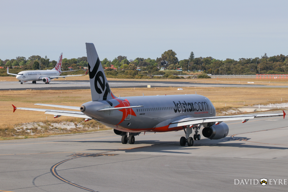 VH-VFD Airbus A320-232 (MSN 4922) of Jetstar, at Perth Airport - 2 November 2017. Taxying out to runway 06 for departure to Melbourne as flight JQ973 at 8:19am. Lined up on runway 06 for take-off is VH-YFE Boeing 737-81D (MSN 39414/3623) of Virgin Australia, named 'Sunshine Beach', departing as VA714 to Adelaide. Photo © David Eyre