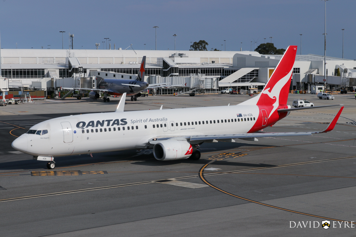 VH-VZA Boeing 737-838 (MSN 34195/2502) of Qantas, named 'Port Augusta', at Perth Airport - 2 November 2017. Taxying out from Terminal 4 at 8:08am as flight QF668 to Adelaide. In the background is VH-VFD Airbus A320-232 (MSN 4922) of Jetstar, at Bay 19 being prepared to return to Melbourne as flight JQ973. Photo © David Eyre