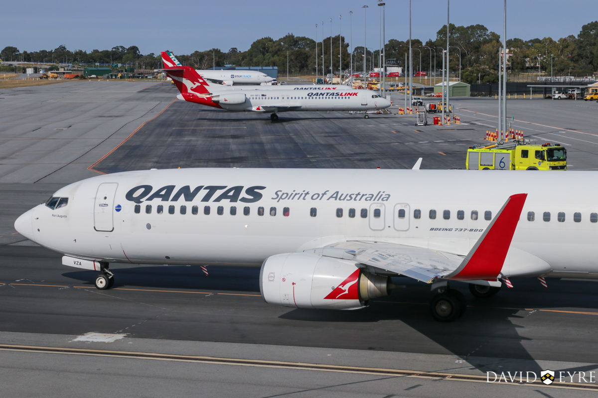 VH-VZA Boeing 737-838 (MSN 34195/2502) of Qantas, named 'Port Augusta', at Perth Airport - 2 November 2017. Taxying out to runway 06 at 8:09am as flight QF668 to Adelaide. In the background are VH-NPU and VH-NQE Fokker 100 of QantasLink (Network Aviation), with Boeing 737-400(SF) VH-XNH and ZK-TLJ at the freight area. Photo © David Eyre