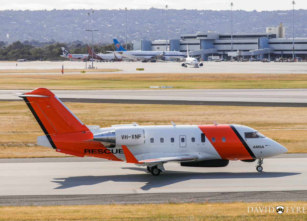 VH-XNF Bombardier CL-600-2B16 Challenger 604 (MSN 5656) owned by Cobham SAR Services Pty Ltd, operated for the Australian Maritime Safety Authority (AMSA), at Perth Airport - 2 November 2017. Taxying out at 8:11am for a search and rescue off Port Denison. Built in 2006, ex C-FOGX, N338FX, C-FIXN, C-GLXY. Terminal 1 International in the background, with 9V-JSJ A320-232 of Jetstar Asia, PK-LBO Boeing 737-9GPER of Batik Air Indonesia, B-8426 Airbus A330-223 of China Southern, and VH-YFE Boeing 737-8FE of Virgin Australia. Photo © David Eyre