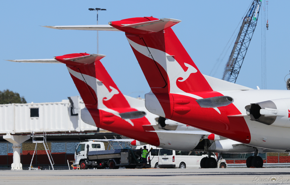 VH-NHJ Fokker 100 (MSN 11464) and VH-NHA Fokker 100 (MSN 11490) of QantasLink (Network Aviation) at Perth Airport - 3 November 2017. VH-NHJ had arrived at 9:36am as NETLINK 1607 from Kalgoorlie and is parked at Bay 19. VH-NHA in the foreground is arriving on Bay 18 at 9:48am as NETLINK 1645 from Paraburdoo. Photo © David Eyre