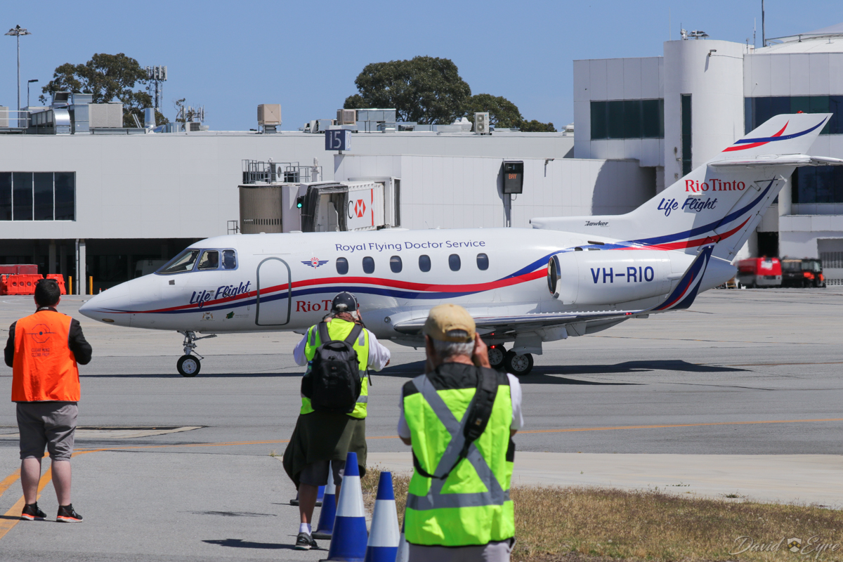 """Aviation Association of Western Australia Inc (AAWA) members photographing VH-RIO Hawker 800XP (MSN 258594) of the Royal Flying Doctor Service (RFDS) / """"Rio Tinto Life Flight"""", at Perth Airport – 3 November 2017. Taxying out to runway 03 at 10:14am to depart to RAAF Curtin at Derby, WA. Photo © David Eyre"""