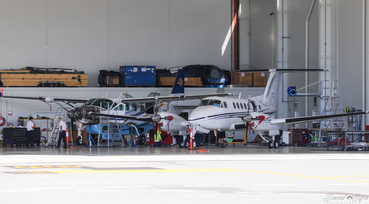 VH-TQV Cessna 208B Grand Caravan EX (MSN 208B5067) of Acena Nominees Pty Ltd, Adelaide, SA, and an unidentified King Air 200 at Perth Airport - 3 November 2017. In the hangar at the end of Taxiway R. VH-TQV was built in 2013, ex XY-AJL, N8153K and was previously operated by Myanmar National Airlines. It arrived in Perth on 16 October 2017. Photo © David Eyre